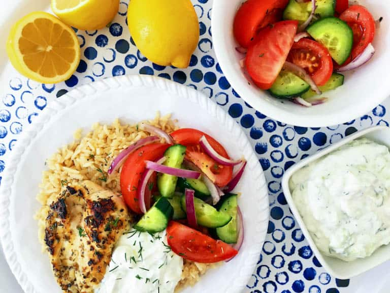 Simple Greek Grilled Chicken Rice Bowl served with a fresh and vibrant salad and delicious tzatziki!