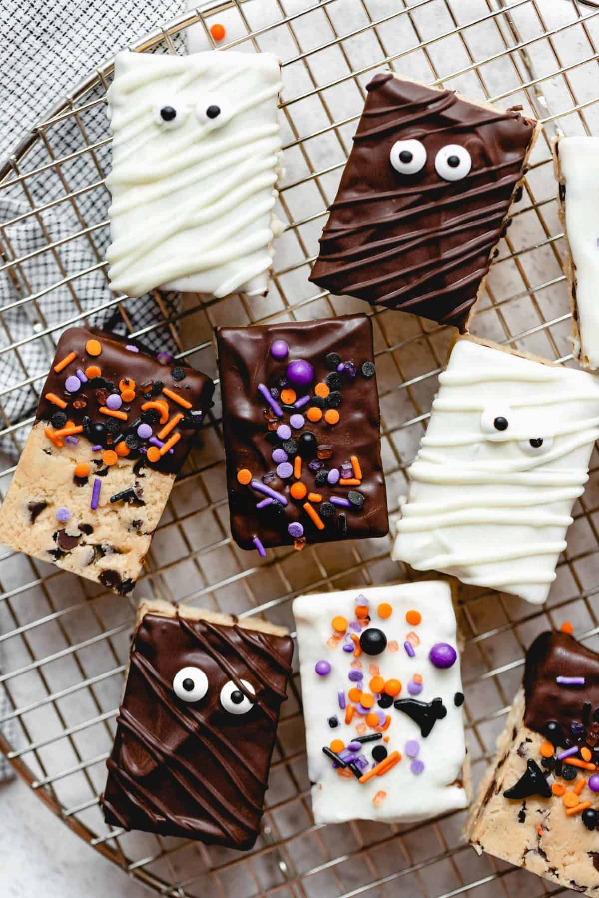 Halloween themed cookie dough rice krispie treats on a wire rack