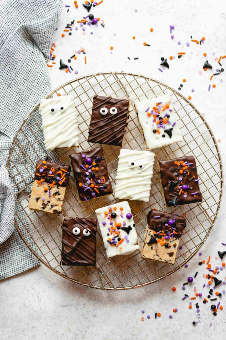 Halloween decorated cookie dough rice krispie treats on a round wire rack