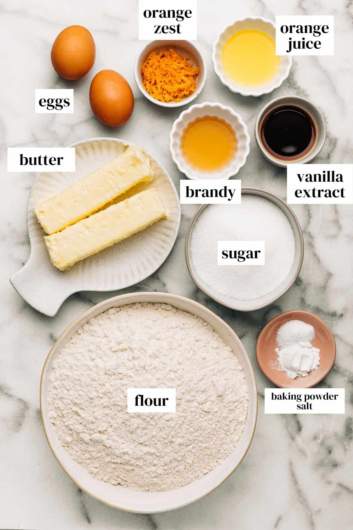 eggs, orange zest, orange juice, brandy, vanilla extract, sugar, butter, baking powder, salt, and flour on a marble surface.