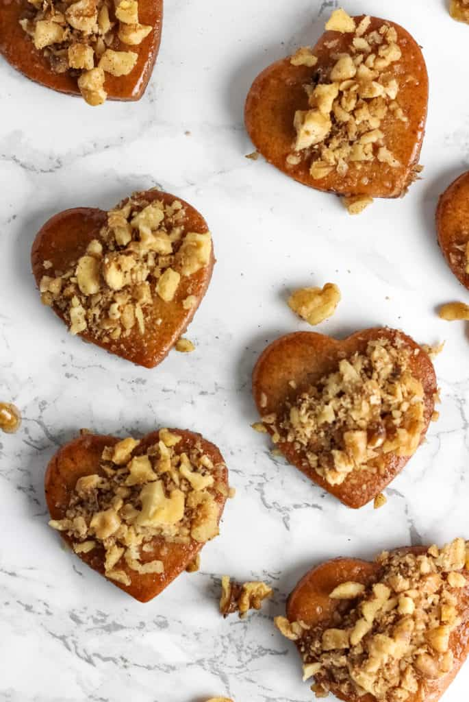 Melomakarona - traditional honey soaked Greek Christmas cookies that are flavored with cinnamon, cloves, and orange and topped with walnuts.