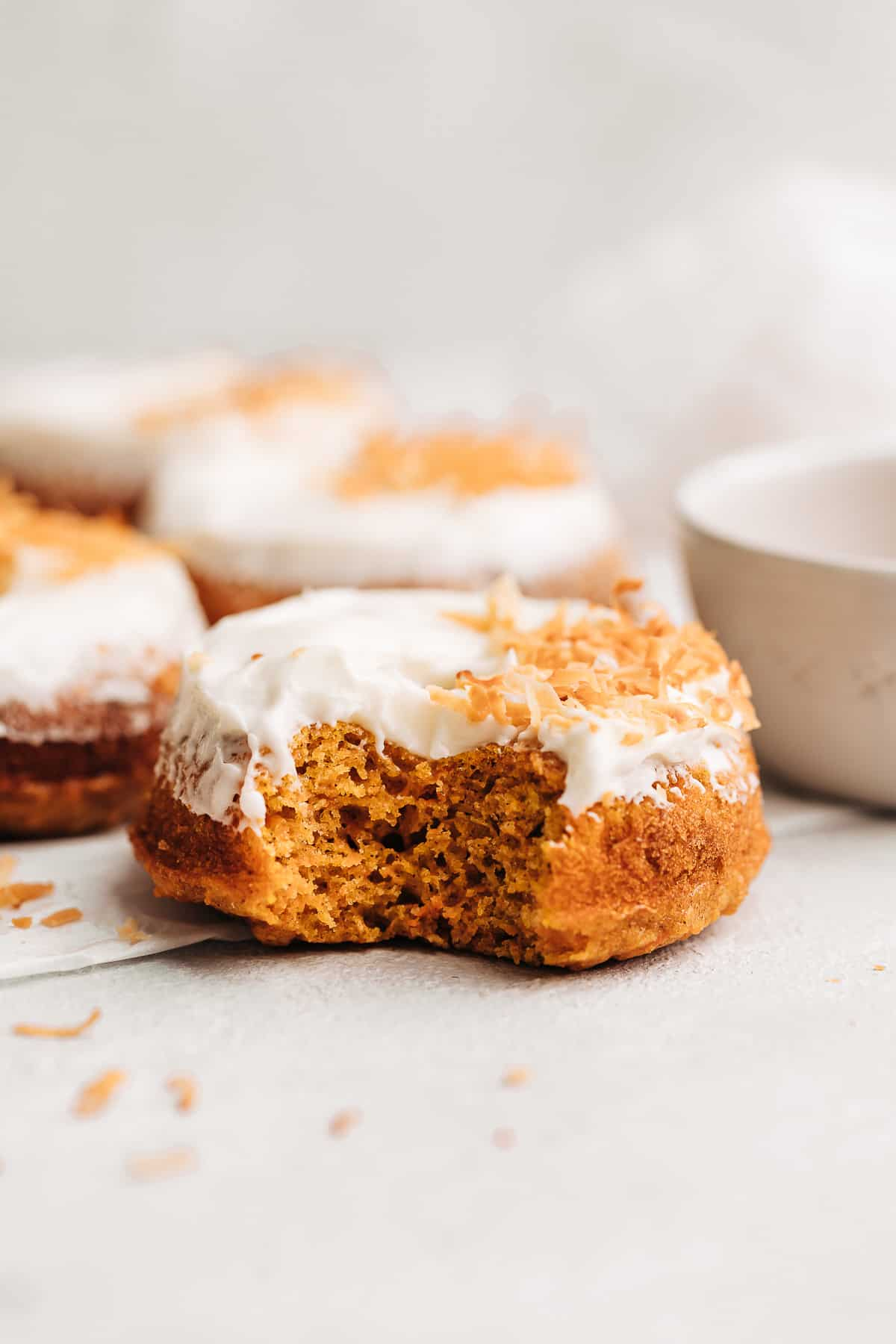 Bite shot of a carrot cake donut with cream cheese frosting and toasted coconut flakes.