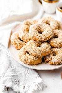 olive oil and sesame seed cookies stacked on a plate