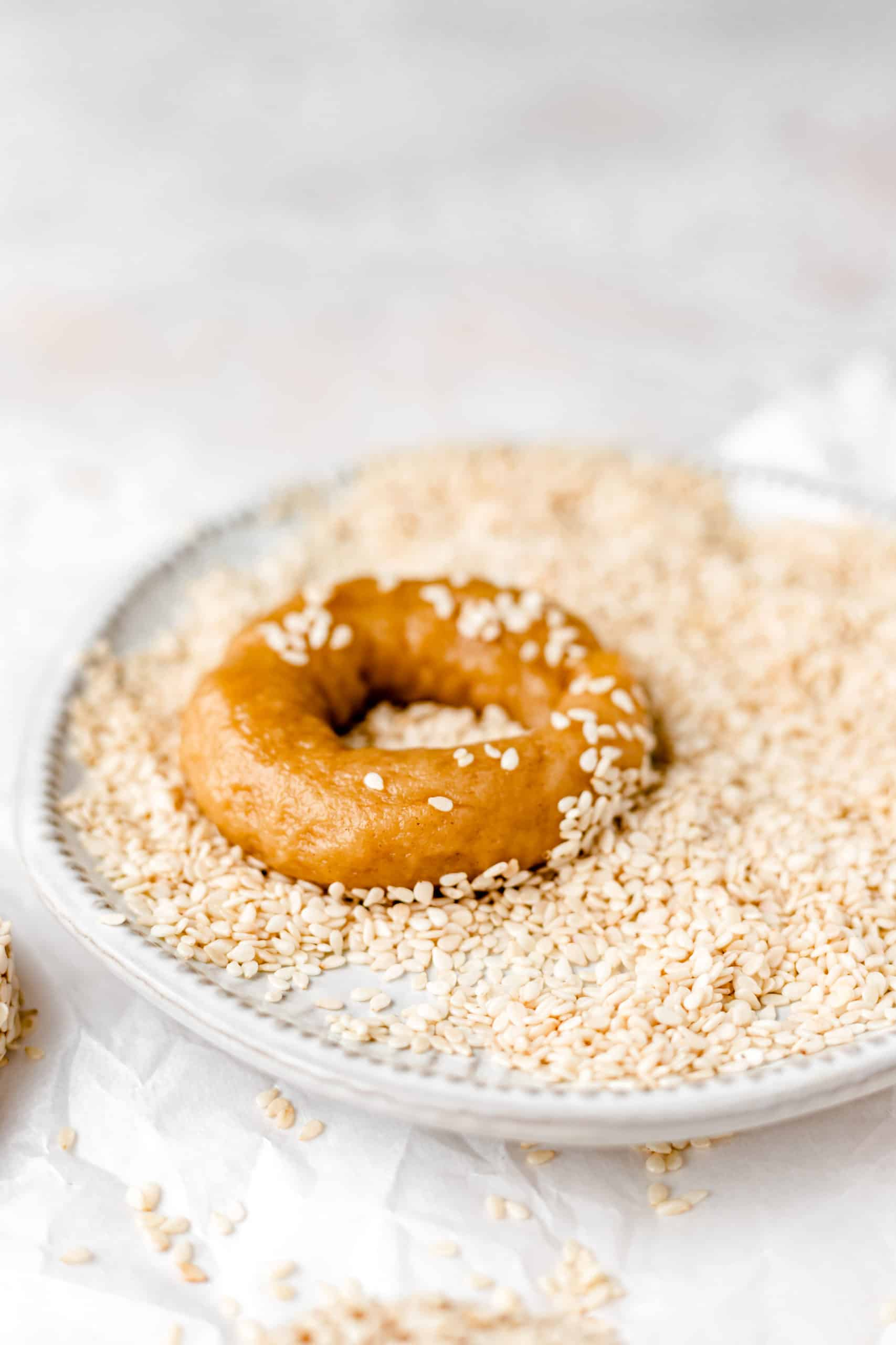 olive oil and orange cookie in a plate of sesame seeds