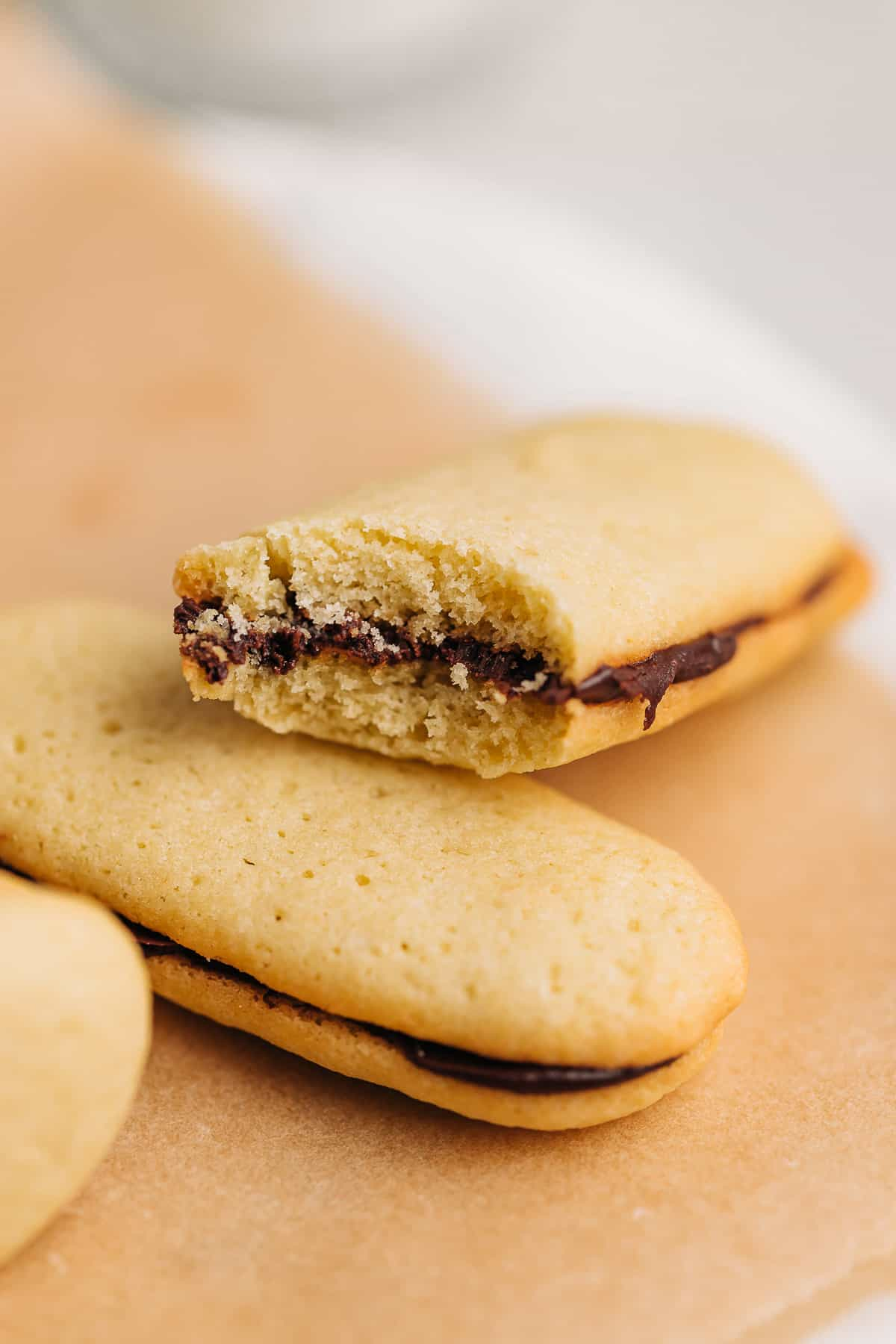 Bite shot of a Milano cookie on brown parchment paper.