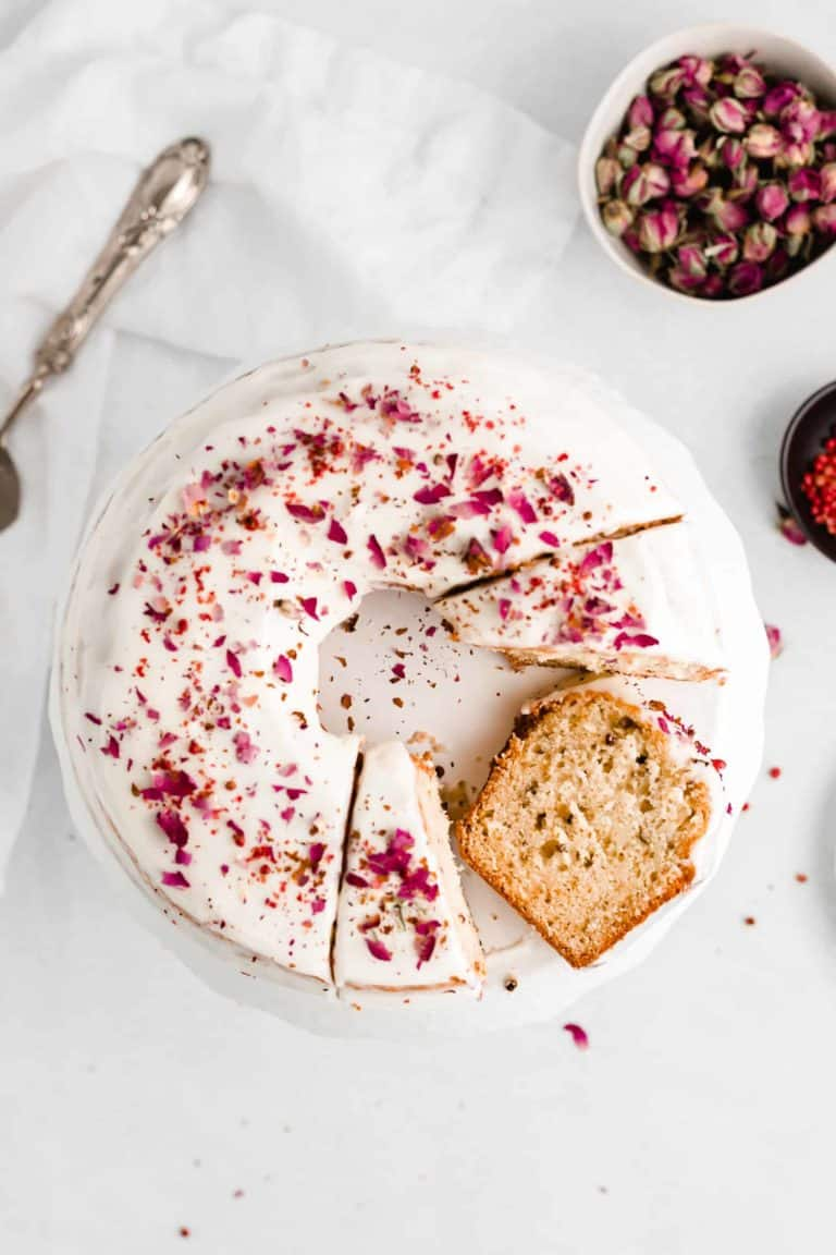 Rose and Pink Peppercorn Cake is delicious, unique, and so pretty! The cake is topped with a cream cheese glaze and finished with crushed pink peppercorns and dried rose buds.