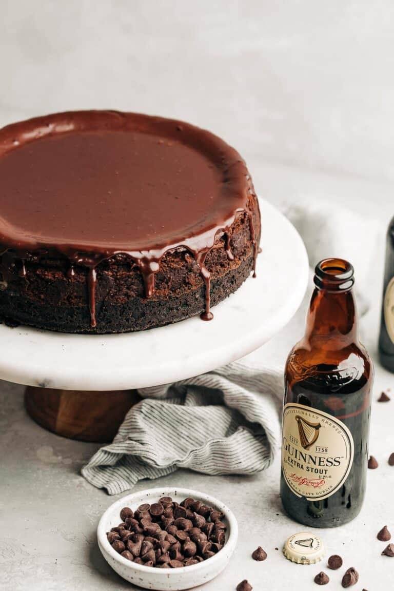 chocolate cheesecake with ganache on a marble cake stand next to a guinness beer bottle and chocolate chips.