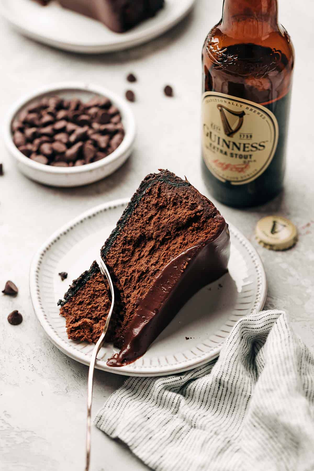 slice of chocolate cheesecake on a plate and a bowl of chocolate chips and bottle of stout.