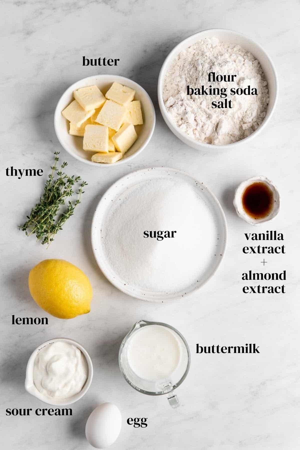 butter, flour, baking soda, salt, vanilla extract, almond extract, buttermilk, sour cream, lemon, sugar, thyme in small bowls.