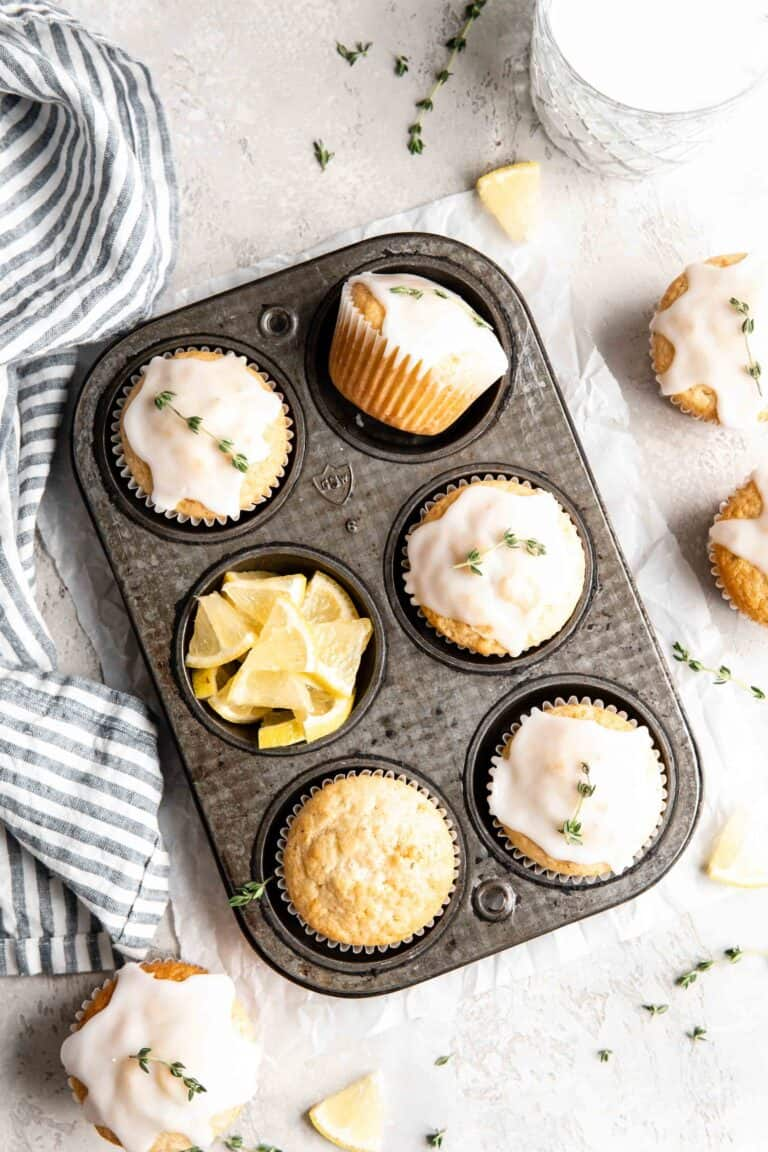 Lemon thyme muffins with glaze in a muffin tin.