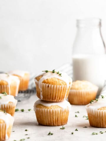 Two lemon thyme muffins with glaze stacked on top of each other.