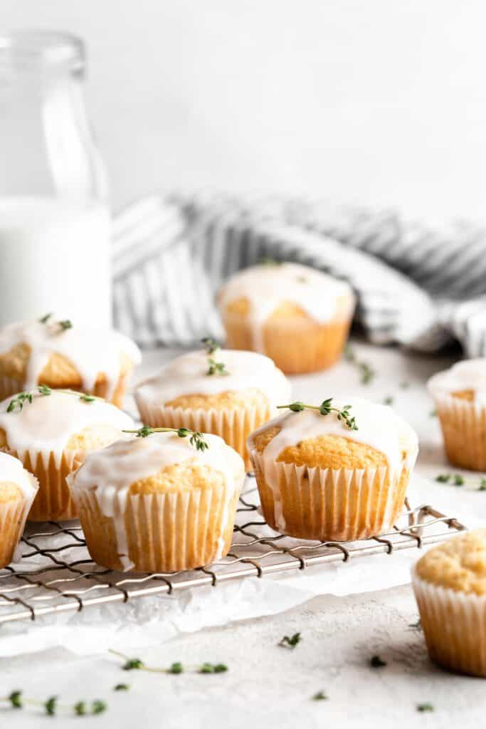 Lemon thyme muffins with glaze on a wire cooling rack.
