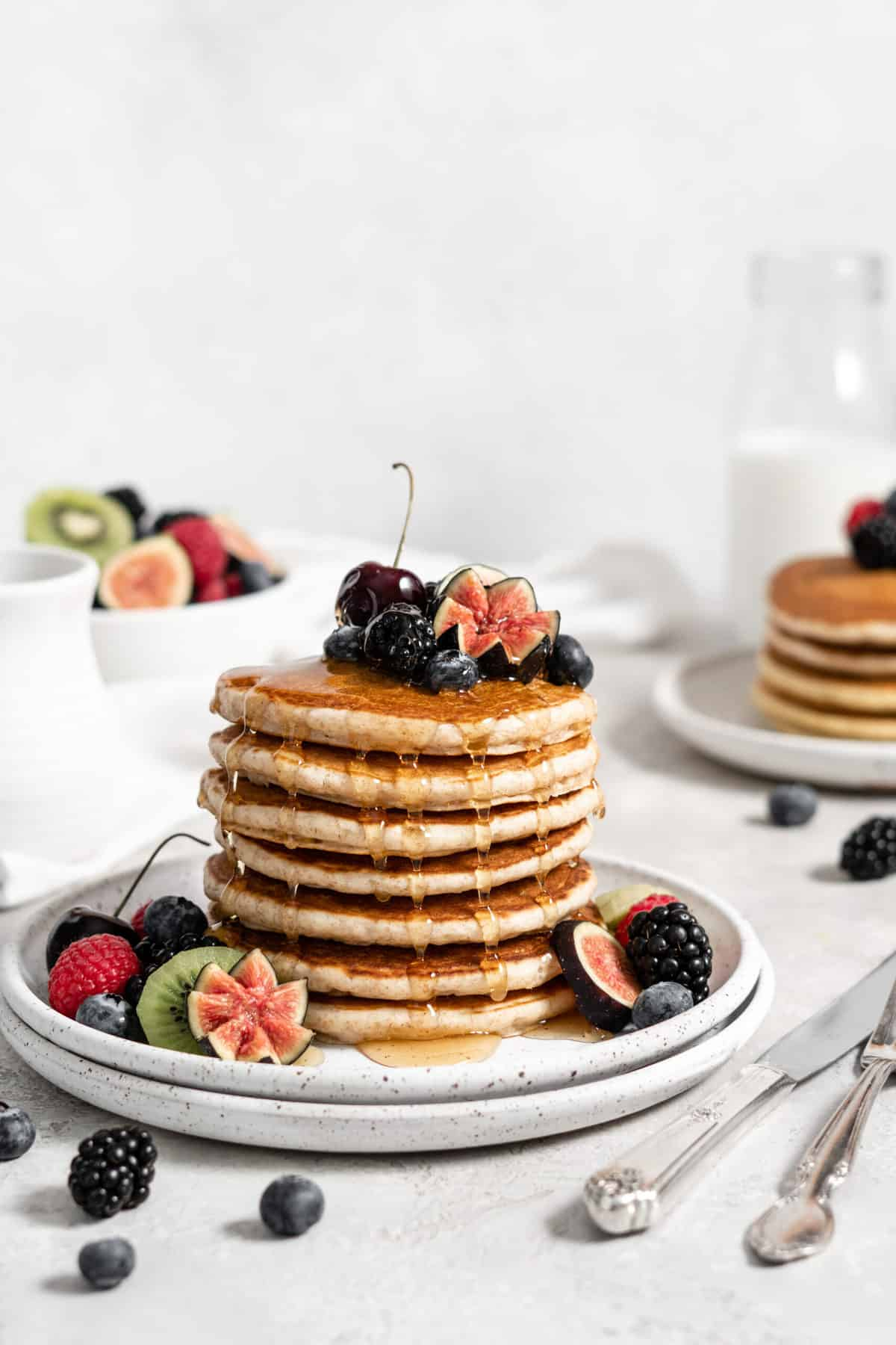 stack of pancakes on a plate with sliced fruit, berries, and maple syrup.