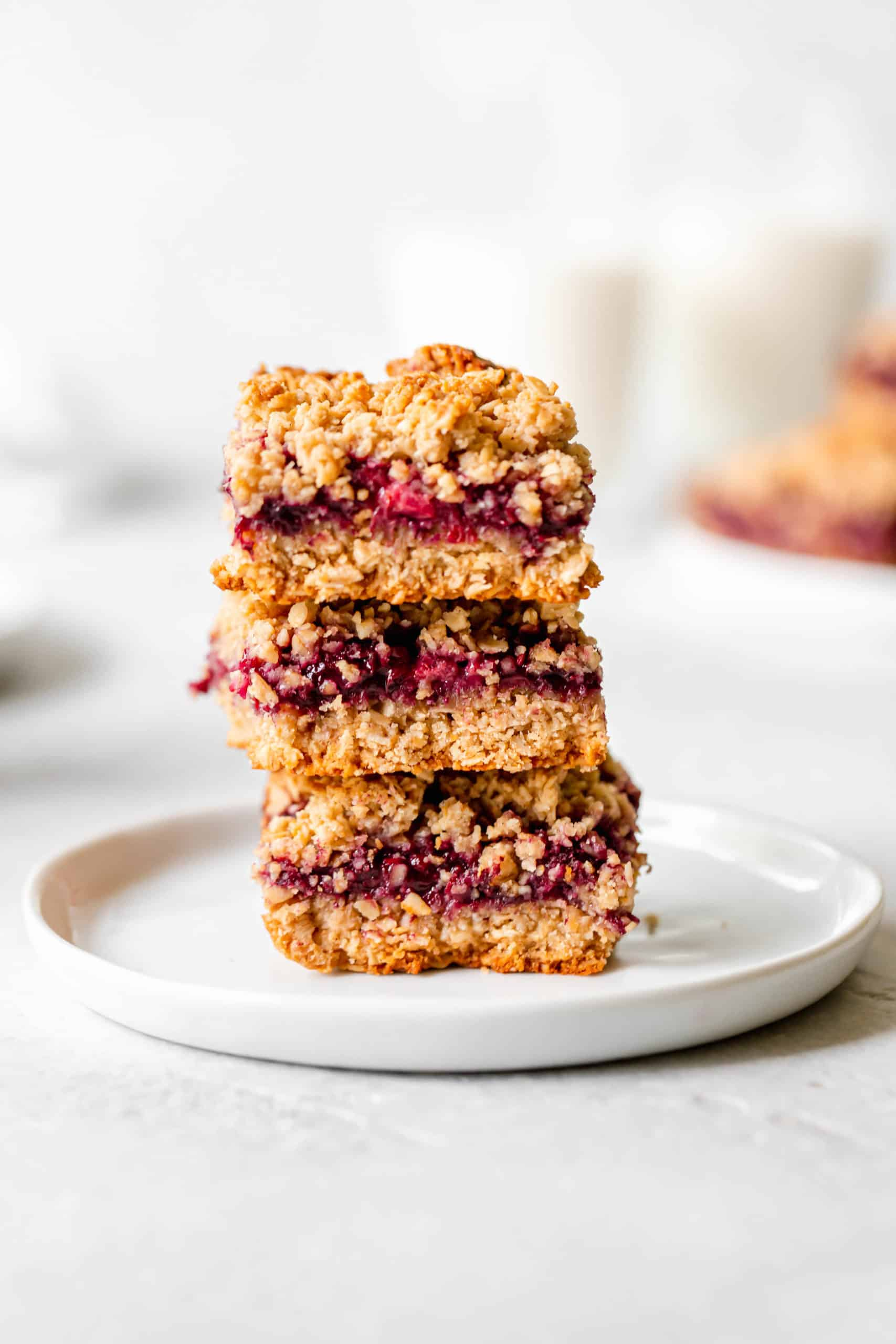 healthy blackberry crumble bars stacked vertically on a plate
