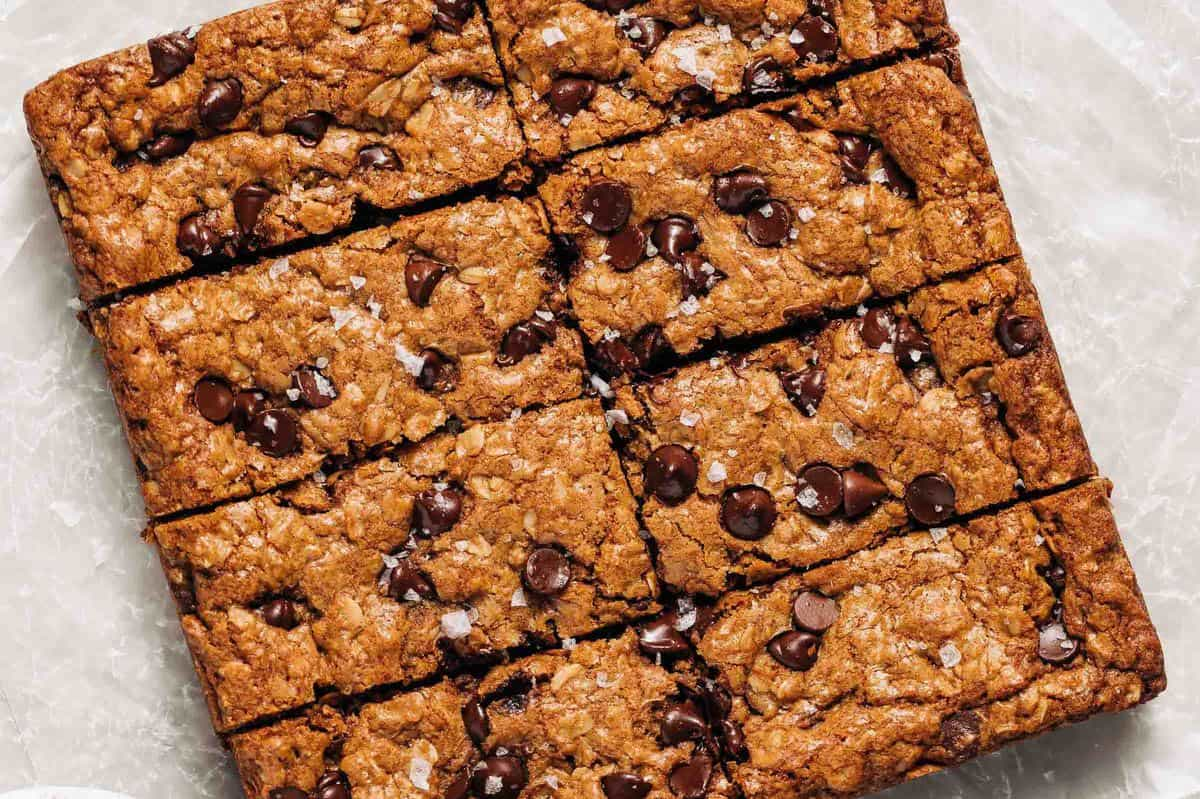 Oatmeal chocolate chip cookie bars on wax paper.
