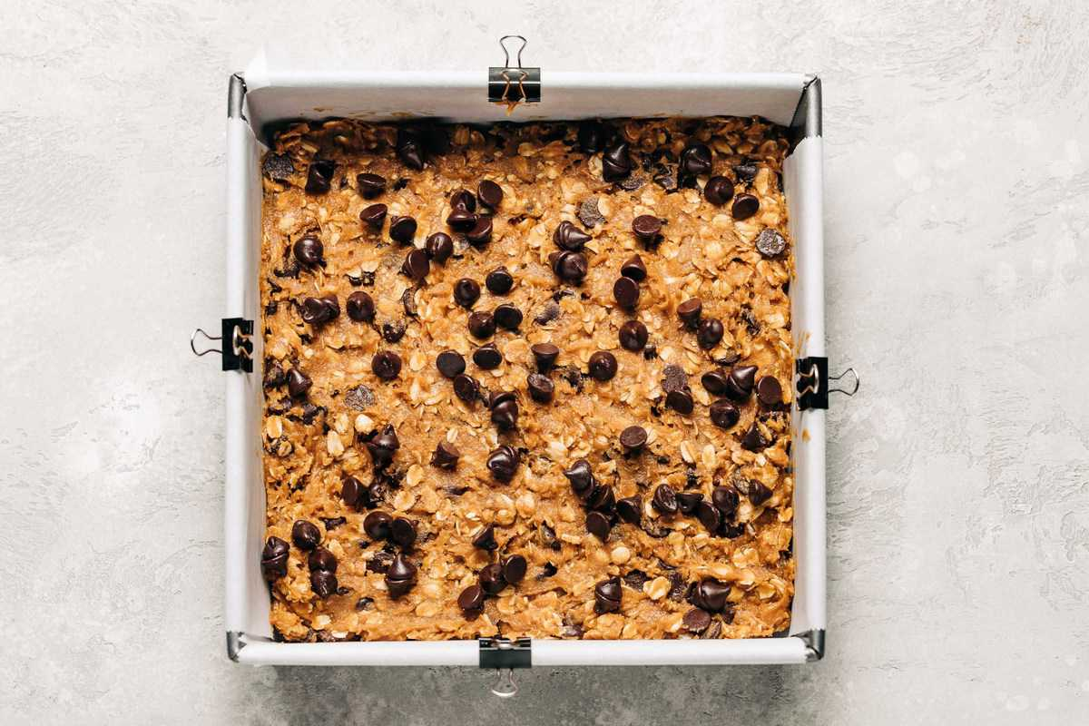 Unbaked oatmeal chocolate chip cookie bars in a baking pan.