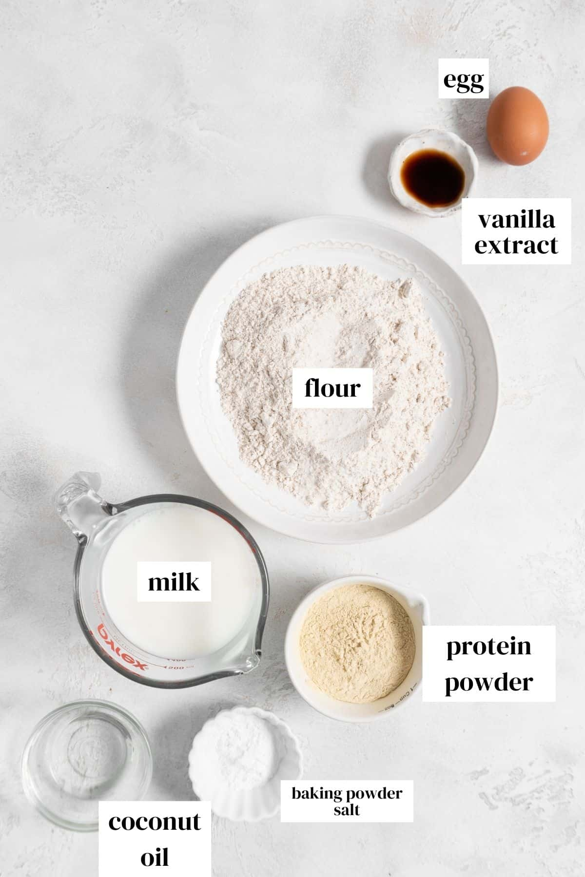 egg, vanilla extract, flour, milk, protein powder, baking powder, salt, and melted coconut oil on a light surface.