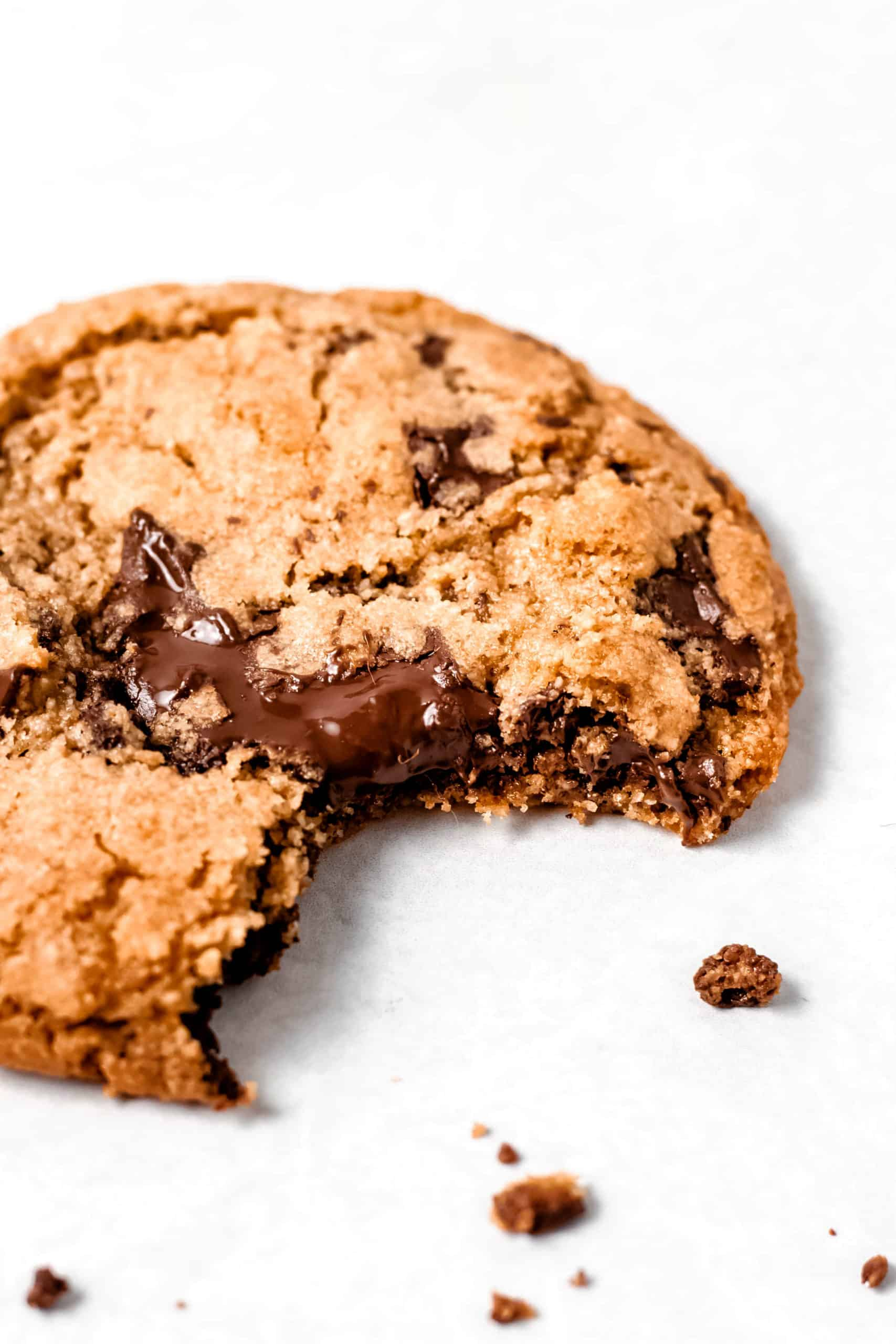 Crisp and chewy gluten free chocolate chip cookie with bite taken out of it