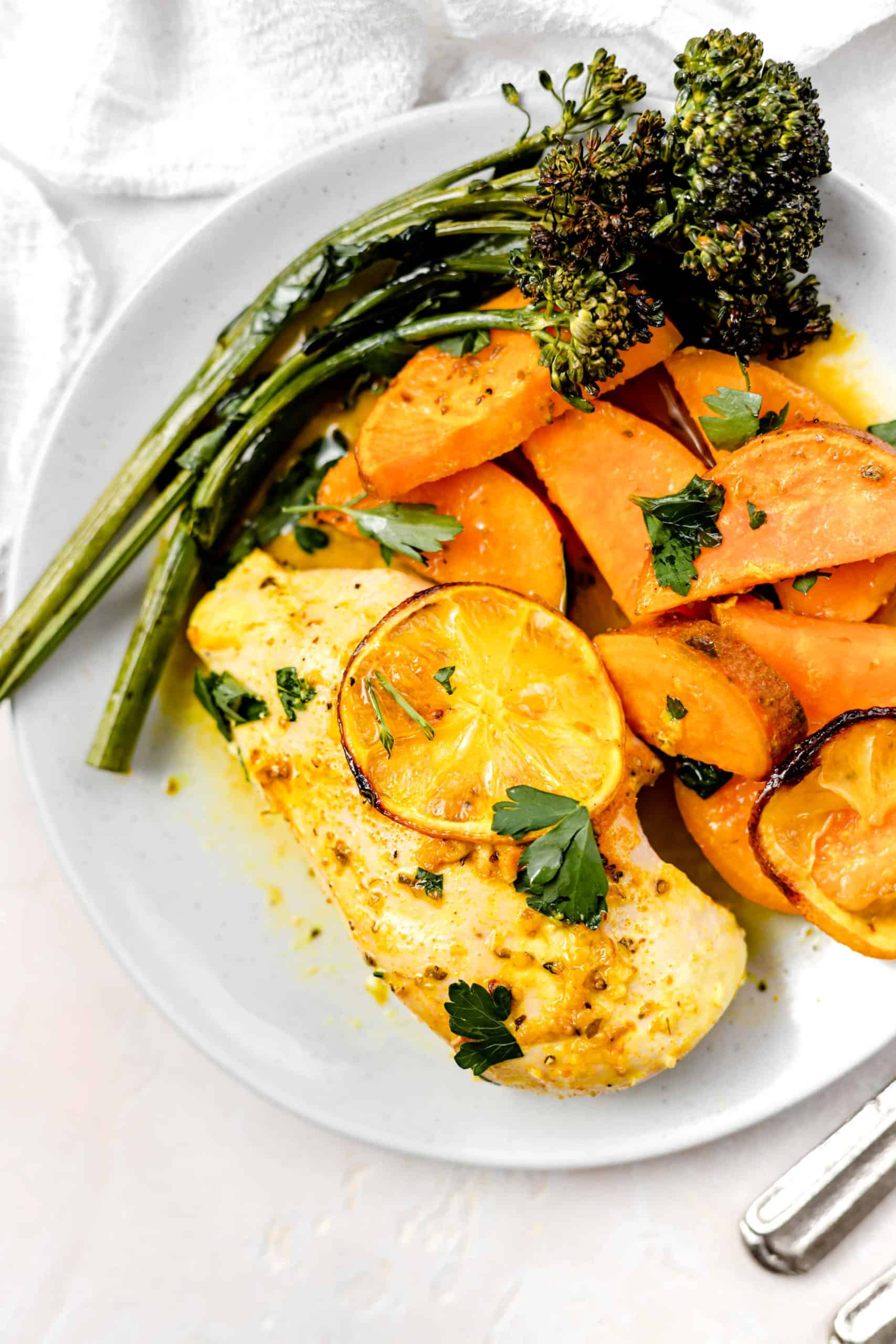 lemon chicken roasted sweet potatoes and broccolini in a plate