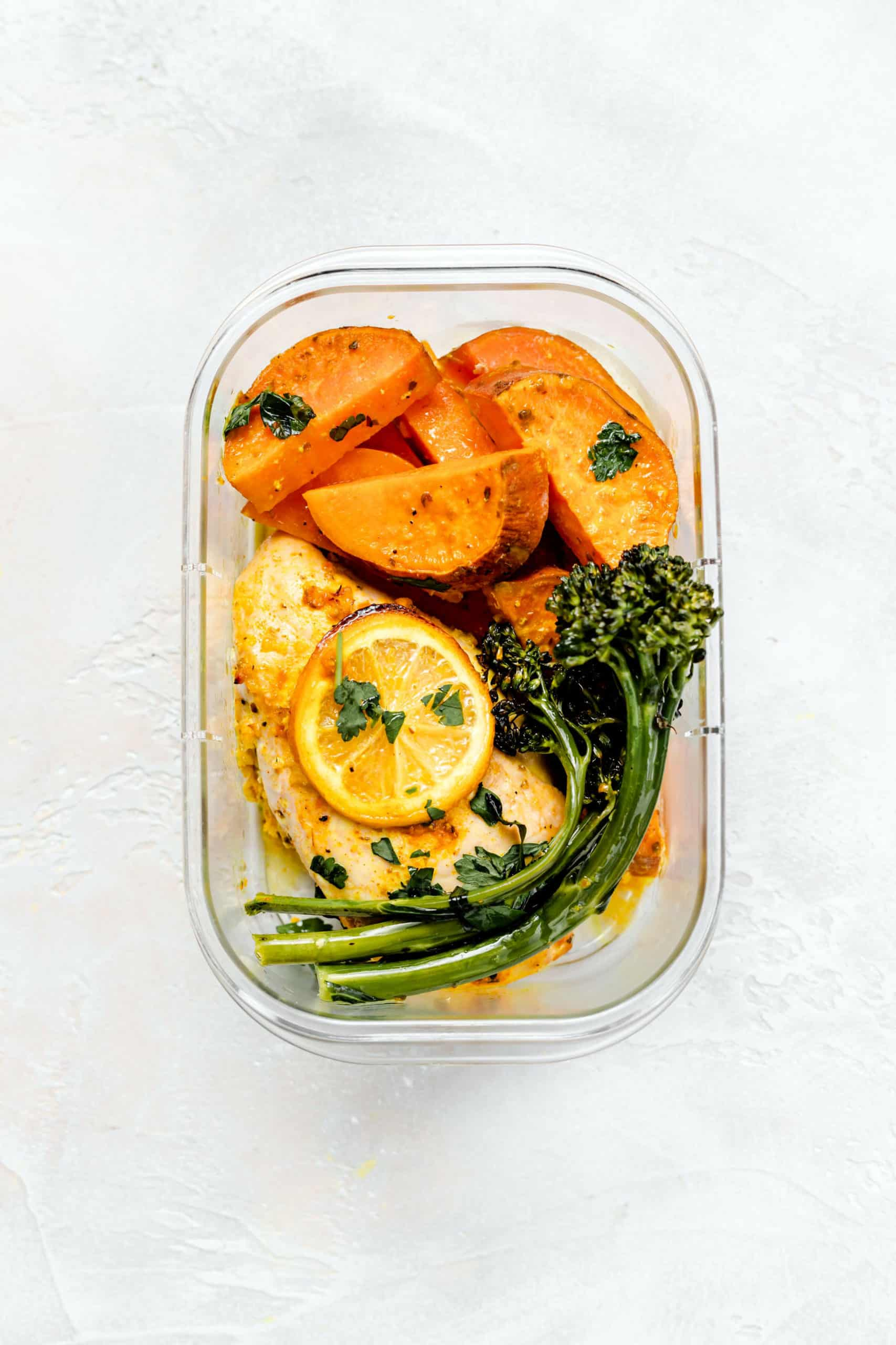 lemon chicken, sweet potatoes, and broccolini in meal prep container