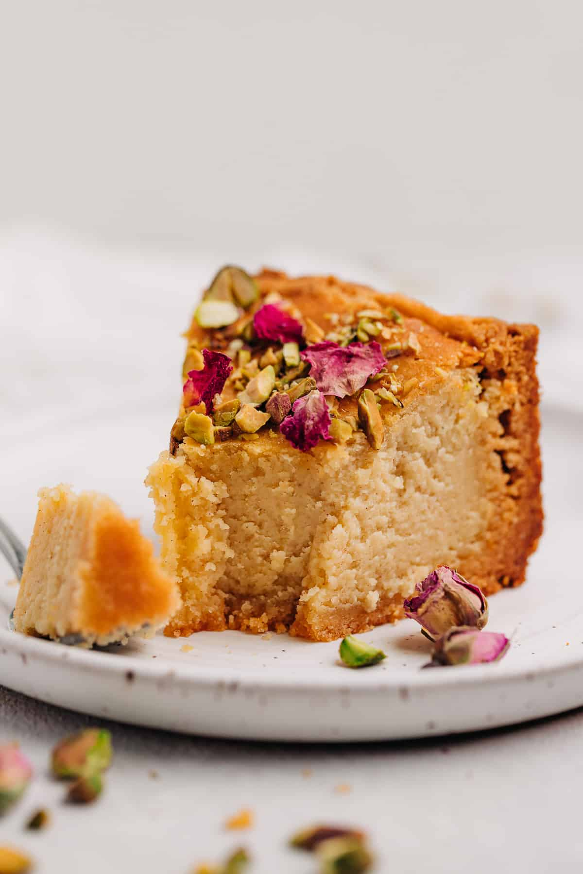 A slice of Persian love cake on a plate with a fork.