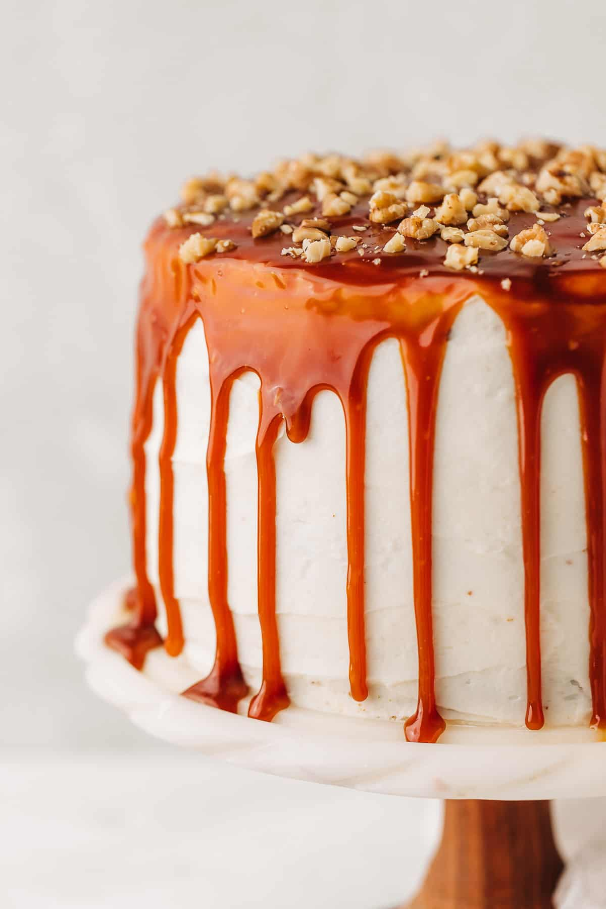 Carrot cake with cream cheese frosting topped with caramel sauce and chopped walnuts on a marble cake stand.
