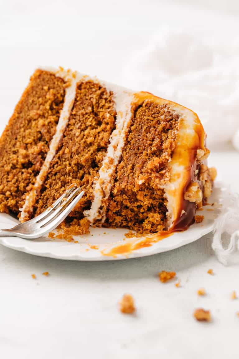 Slice of carrot cake with cream cheese frosting on a white plate.
