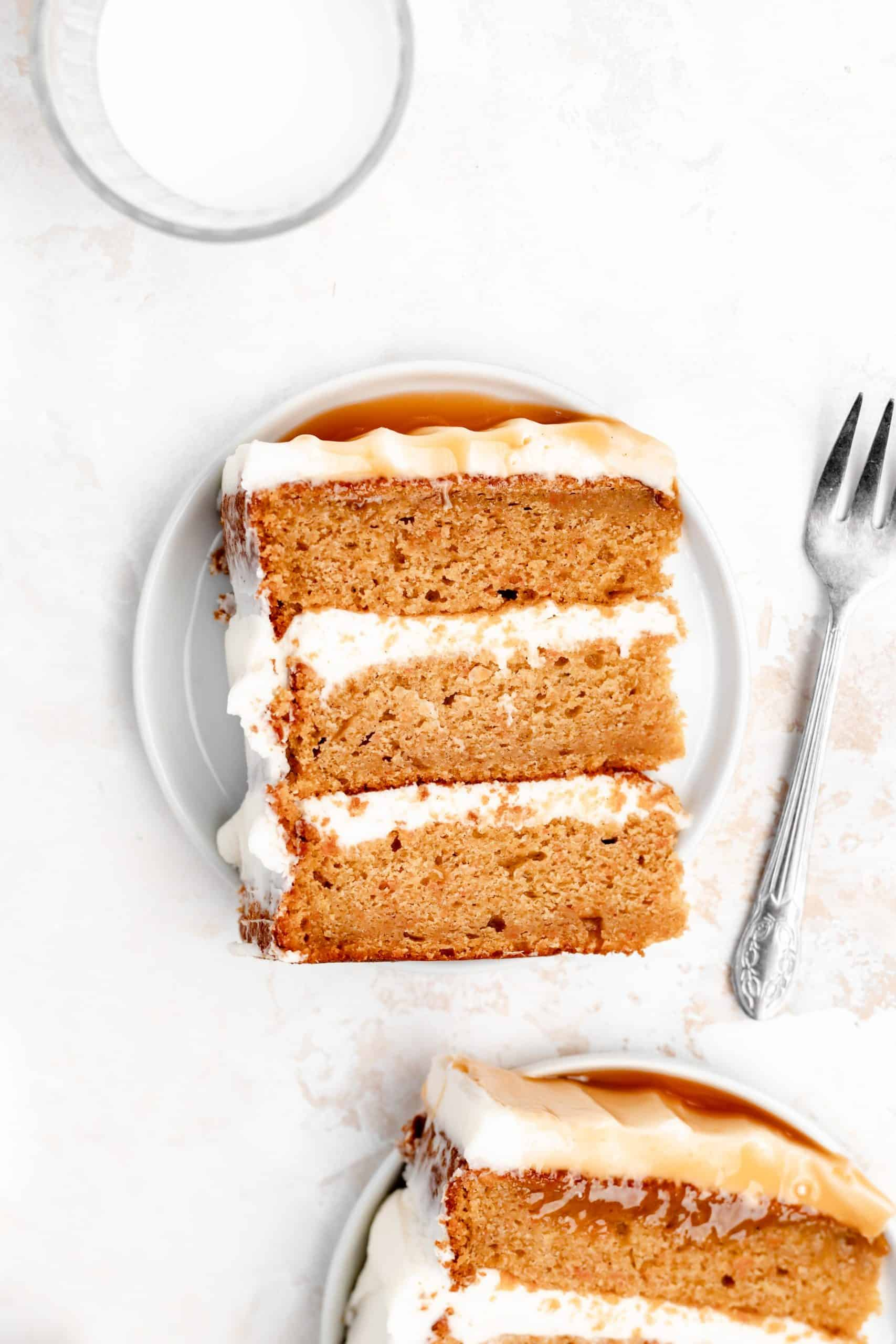 Slice of moist carrot cake with cream cheese frosting on a plate