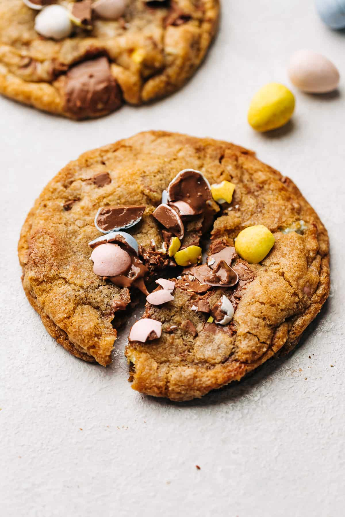 Cadbury Mini Egg milk chocolate chip cookie cut in the center.