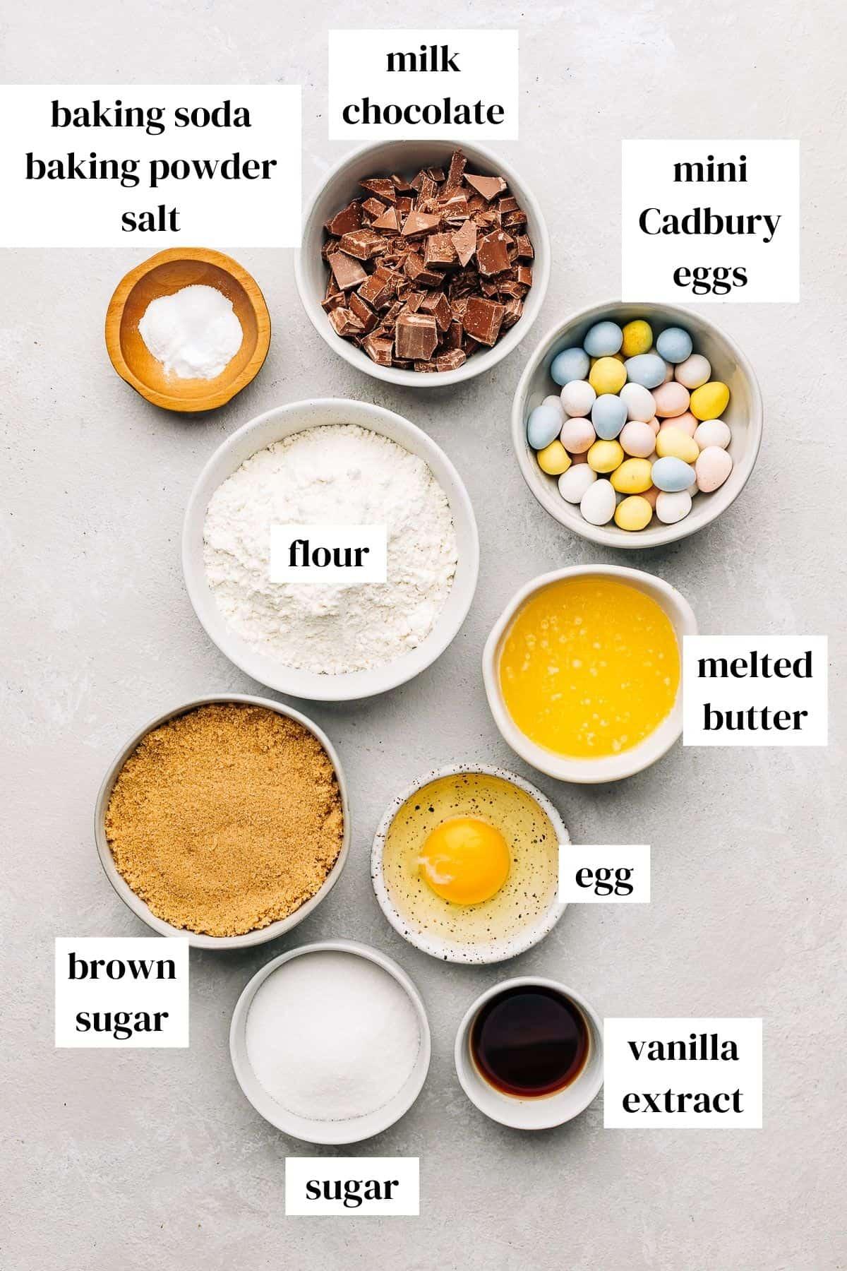 milk chocolate, cadbury mini eggs, melted butter, egg, vanilla extract, sugar, brown sugar, flour, baking powder, baking soda, salt on a gray surface.