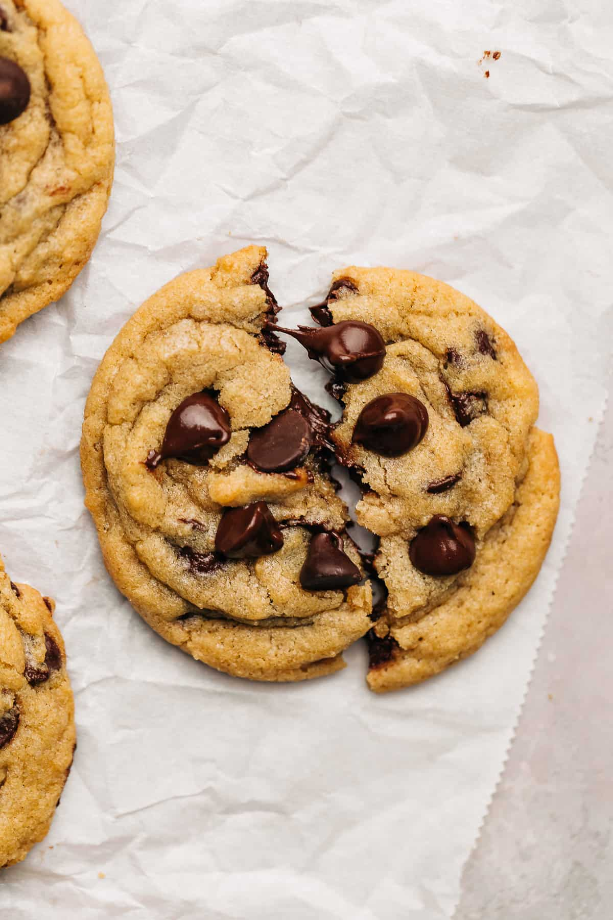 chocolate chip cookie cut in half on parchment paper.