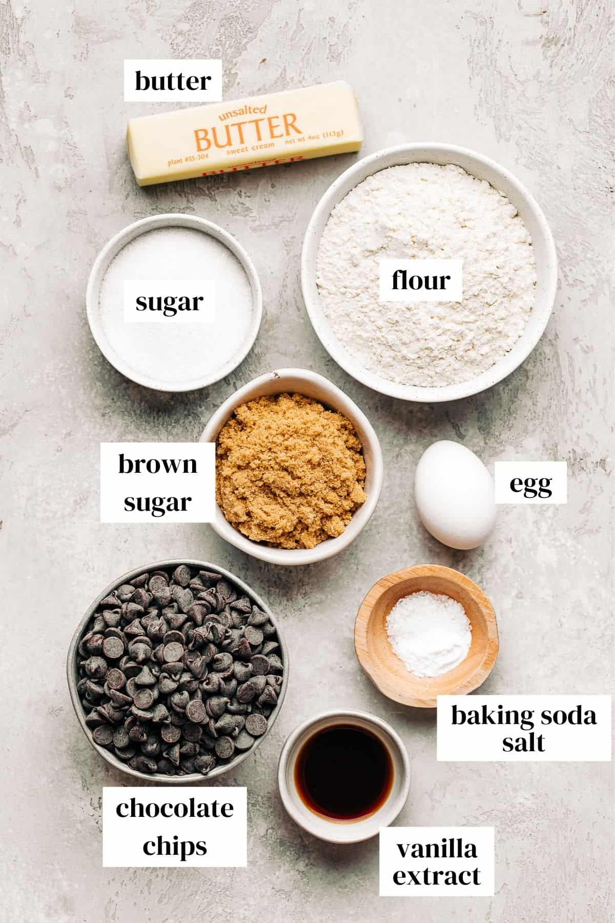 butter, flour, sugar, brown sugar, egg, chocolate chips, baking soda, salt, and vanilla extract in small bowls.