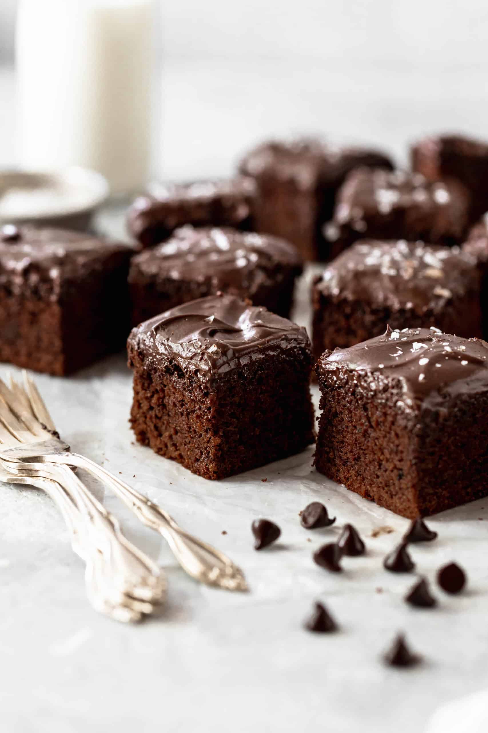 chocolate cake pieces with chocolate frosting on parchment paper