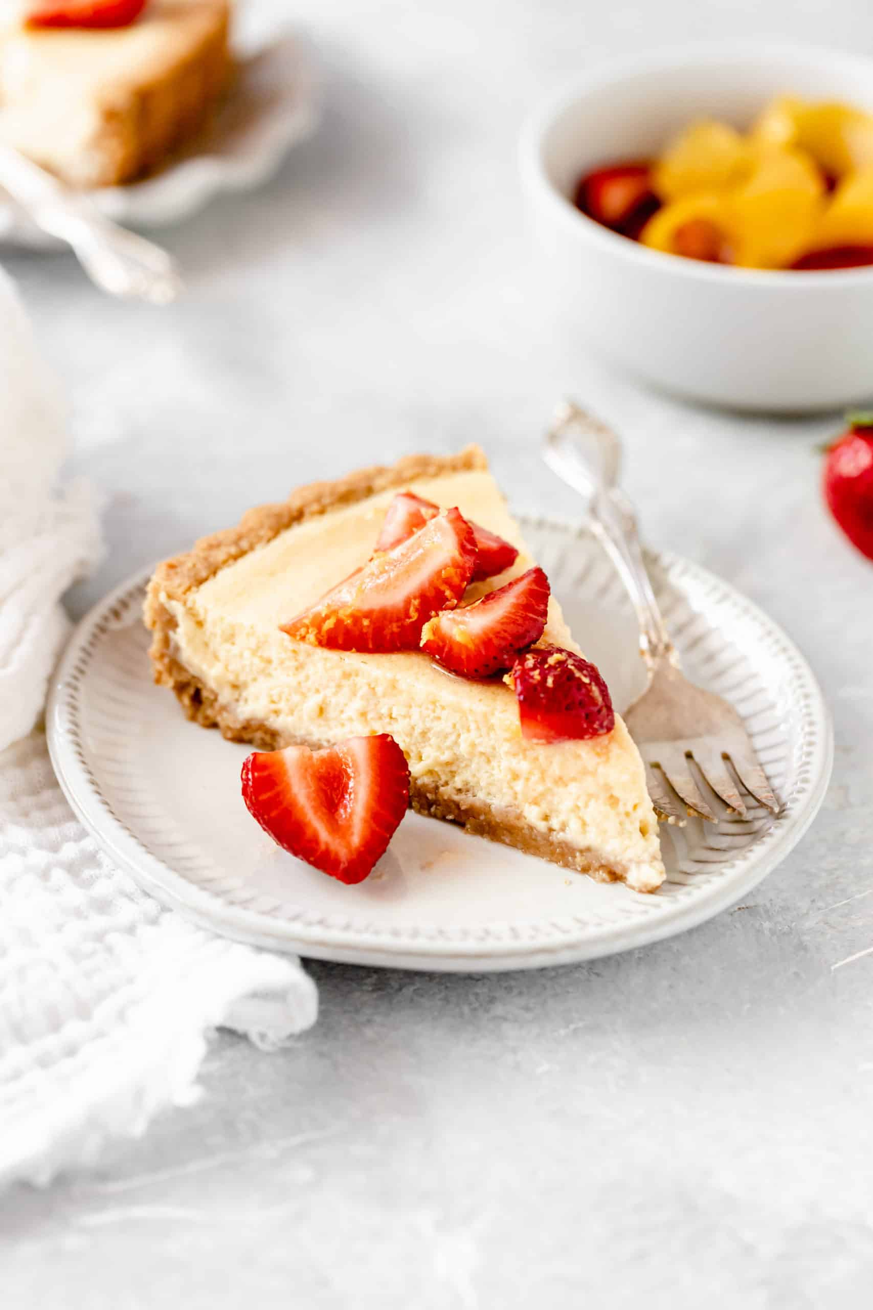 slice of lemon tart with strawberries slices on top