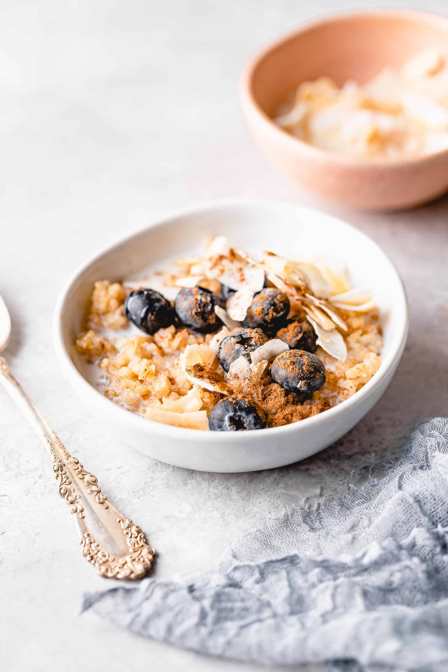 bulgur breakfast bowl topped with coconut flakes, blueberries, cinnamon, and honey