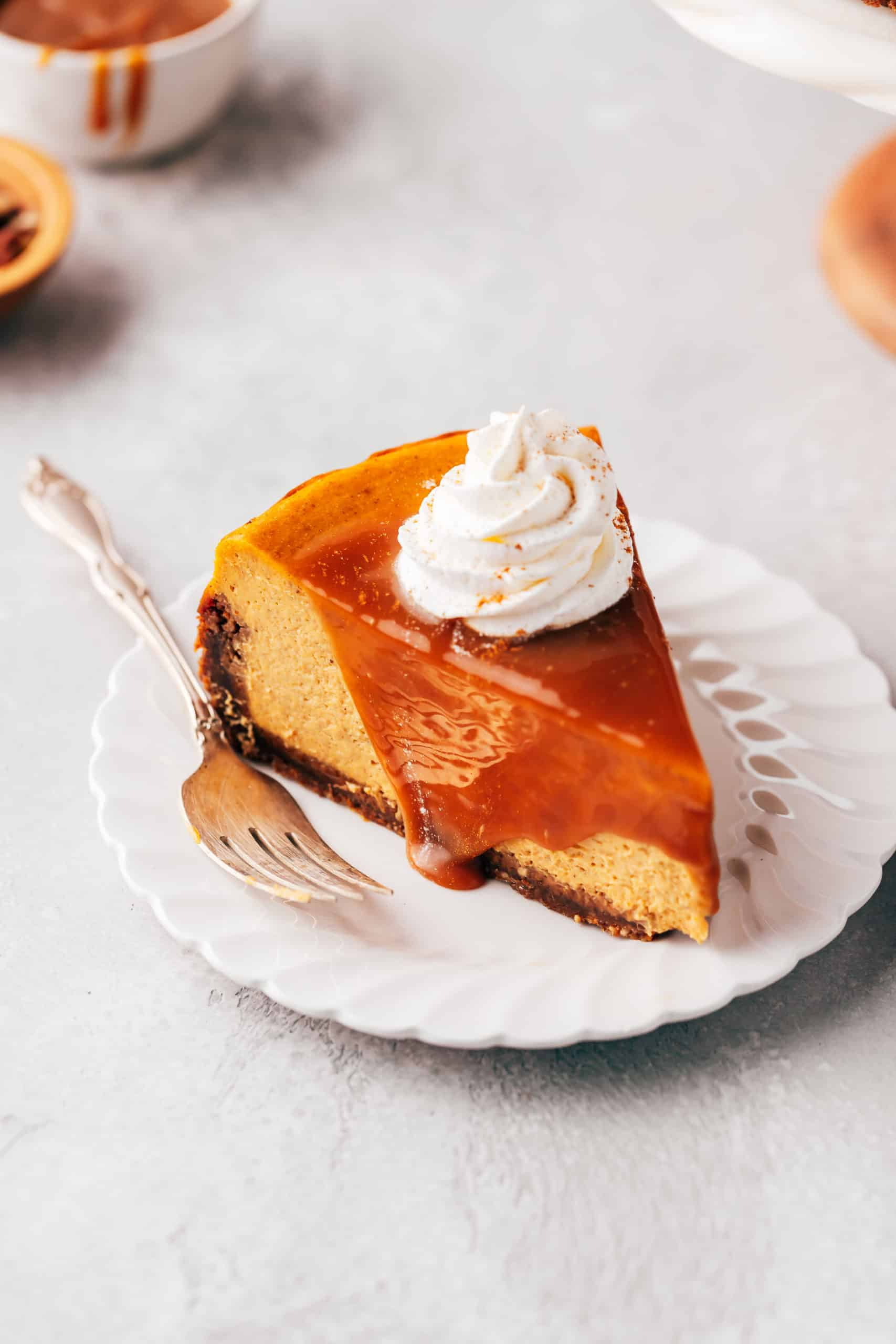 slice of pumpkin cheesecake with caramel sauce and whipped cream on a plate