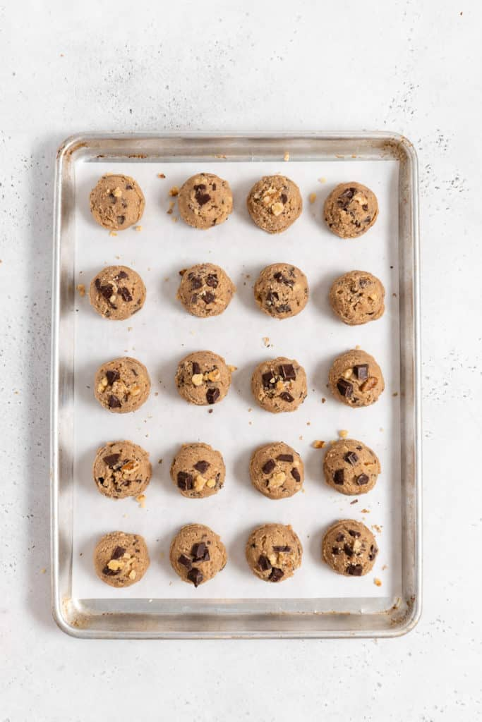 unbaked chocolate chip cookie dough balls on a parchment paper lined baking sheet