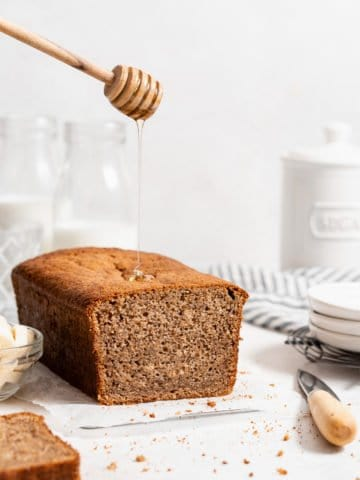 loaf of whole wheat banana bread with a honey drizzle.