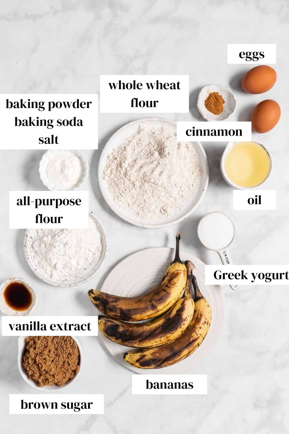 eggs, cinnamon, oil, yogurt, whole wheat flour, all purpose flour, bananas, vanilla, brown sugar on a marble surface.