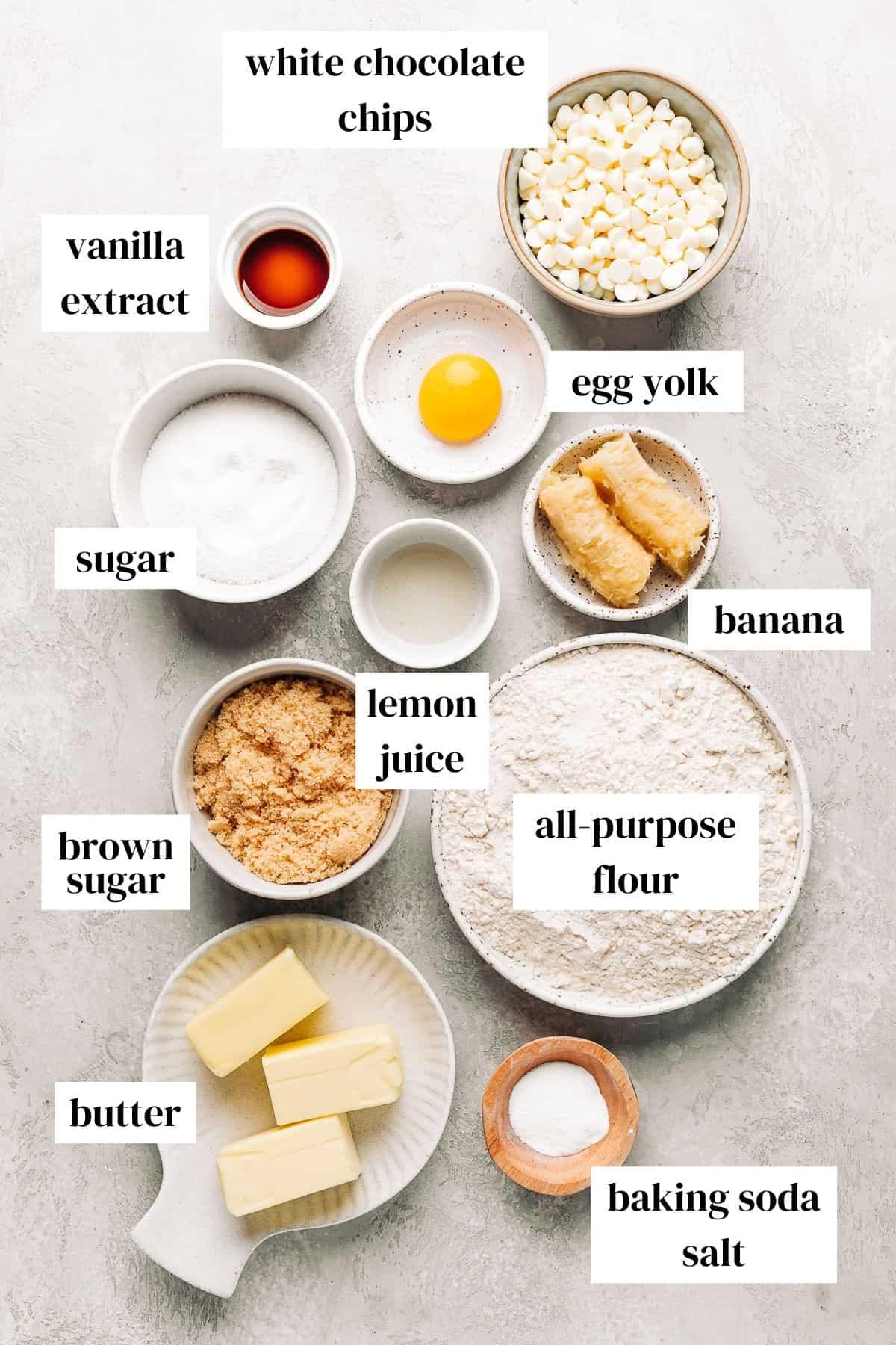vanilla extract, white chocolate chips, egg yolk, banana, sugar, lemon juice, flour, brown sugar, butter, and salt on a grey background.