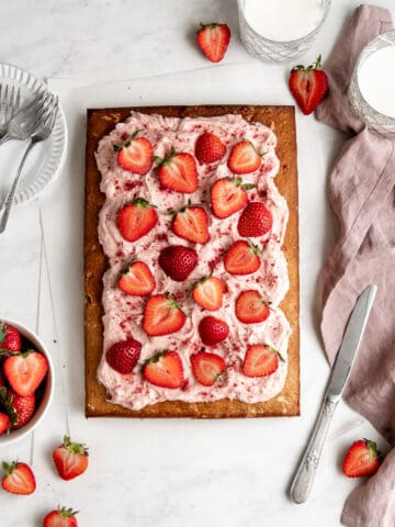 Strawberry sheet cake with strawberry cream cheese frosting topped with sliced strawberries.