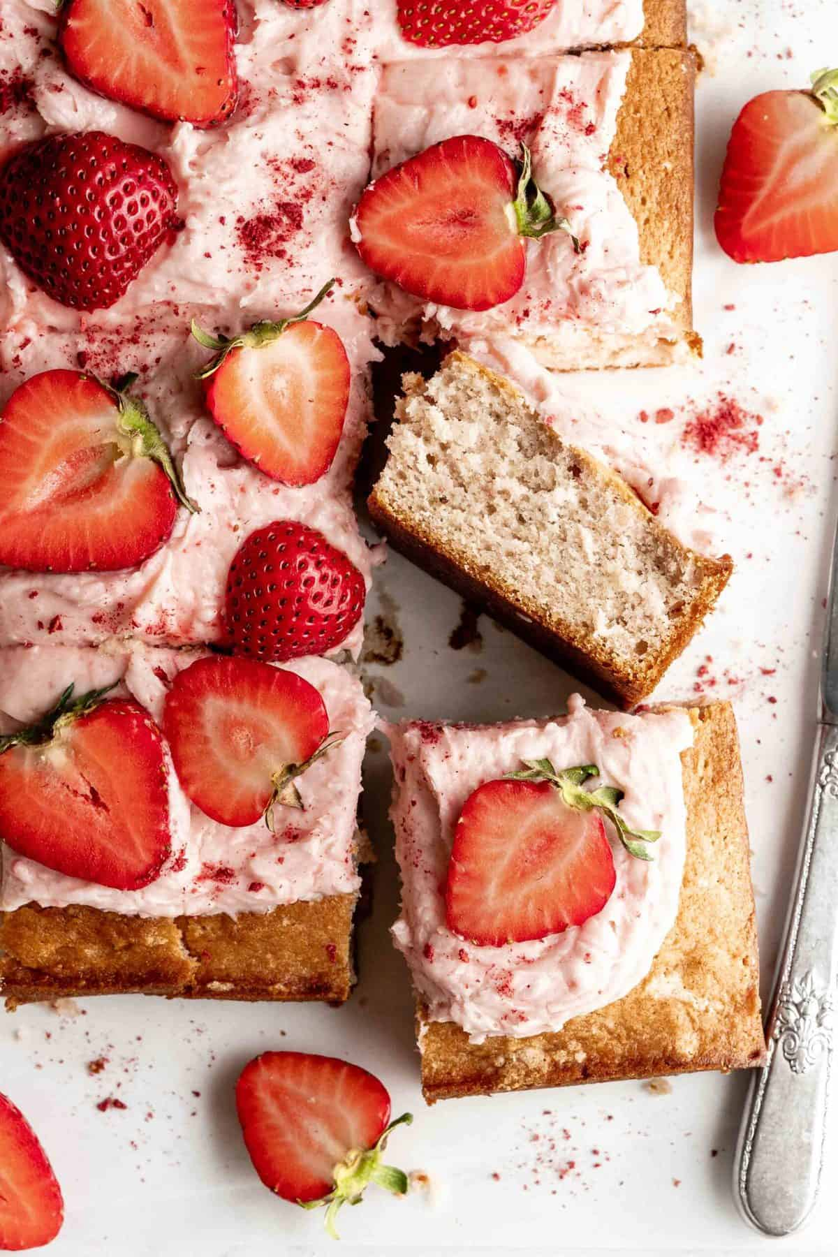 Slice of strawberry sheet cake with strawberry cream cheese frosting topped with sliced strawberries.