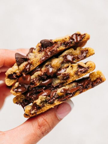 Hand holding stack of chocolate chip cookies cut in half.