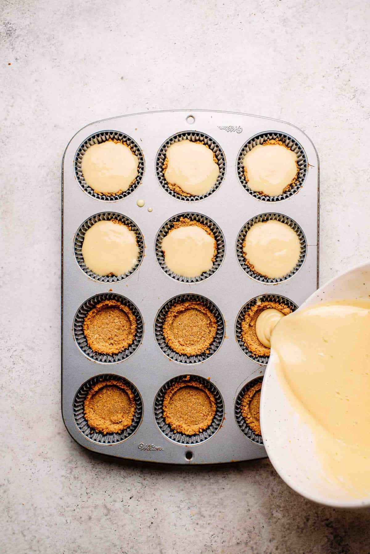 Key lime pie filling poured into mini graham cracker crusts.