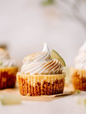 Mini key lime pie with meringue and a slice of lime on brown parchment paper.
