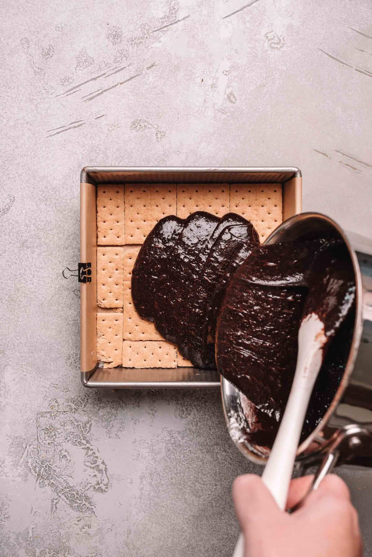 Brownie batter poured over graham crackers in a baking pan.