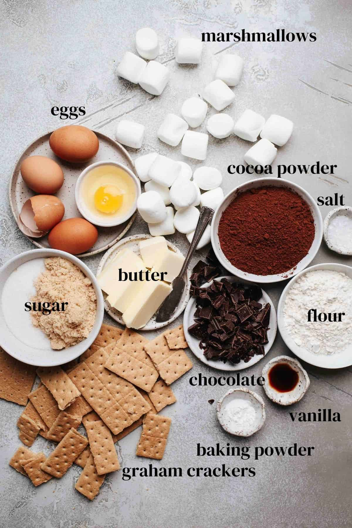 Marshmallows, eggs, sugar, butter, cocoa powder, salt, flout, chocolate, vanilla, graham crackers on a gray surface.
